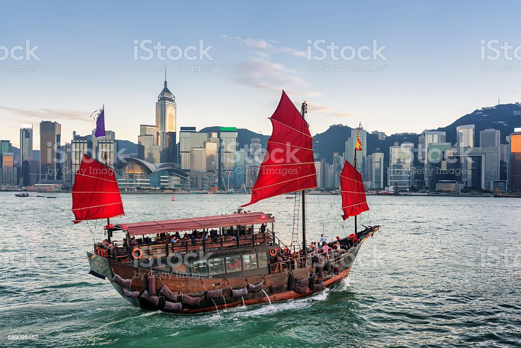 Tourists on sailing ship with red sails crosses Victoria harbor stock photo