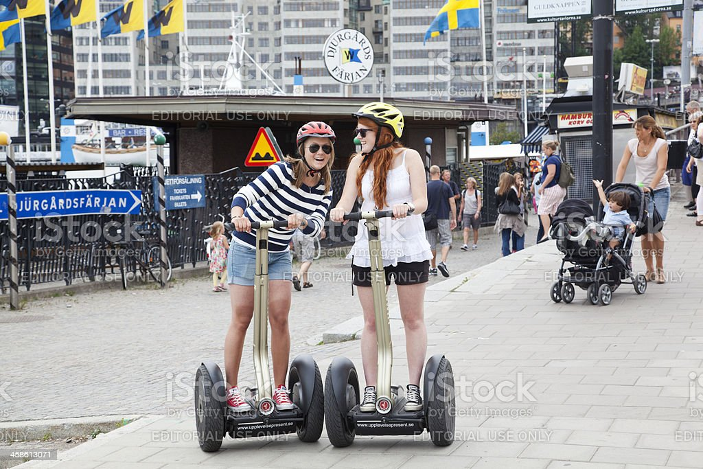 Tourists on Skeppsbron Stockholm in the summer trying out Segways. stock photo