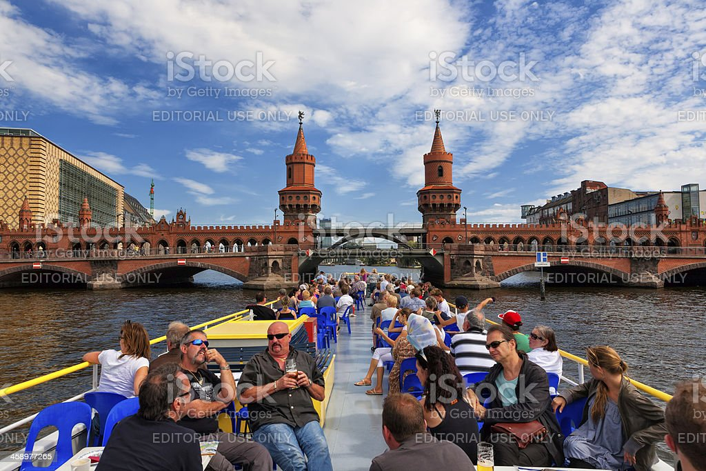 Tourists on the Tourboat approaching Oberbaumbrücke bridge in Berlin Germany stock photo