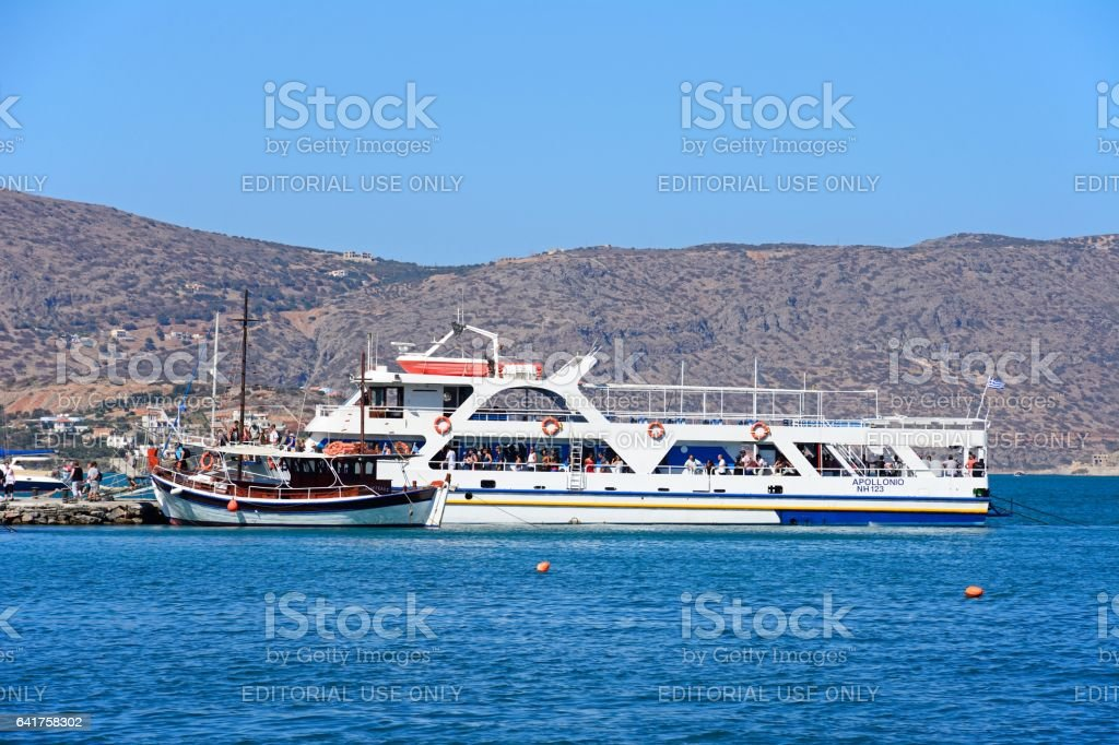 Tourists on tour boats in the harbour, Elounda. stock photo