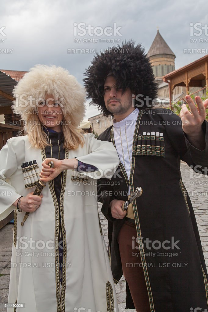 Tourists pose for photos in Georgian traditional attire stock photo