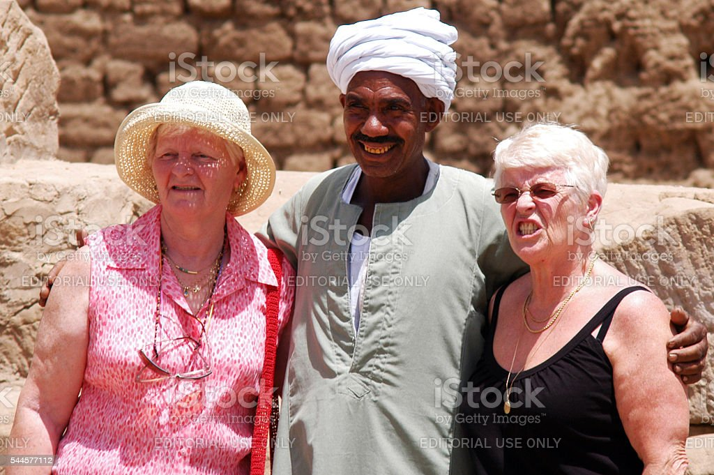 Tourists Post with Egyptian Man in Edfu Temple, Egypt stock photo