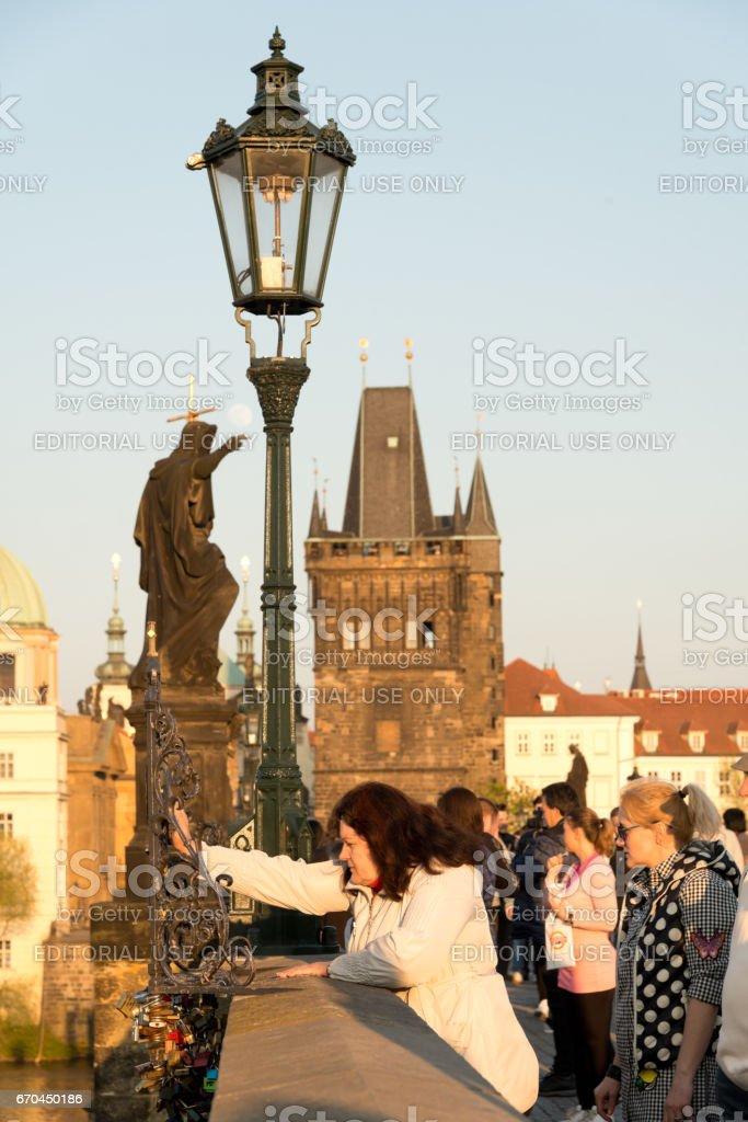 Tourists praying on the Charles Bridge /John of Nepomuk, Prague stock photo