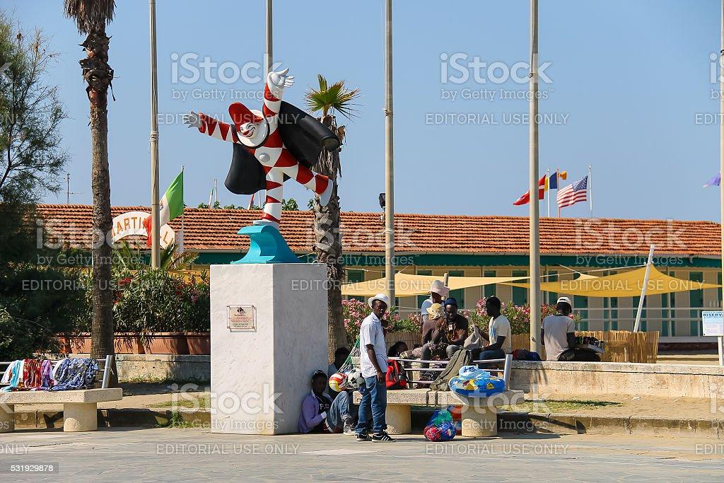 Tourists resting near the statue of Burlamacco. Viareggio, Italy stock photo