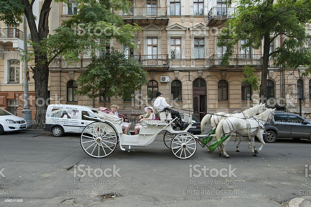 Tourists ride on horse carriage along street in Odessa, Ukraine. stock photo