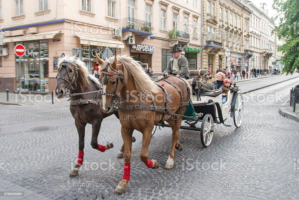 Tourists ride on horse carriage near square Rynok, Lviv, Ukraine. stock photo
