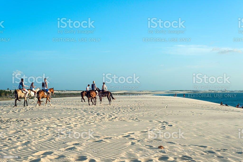 Tourists ride on horseback at Sunset Dune, Jericoacoara, Brazil stock photo