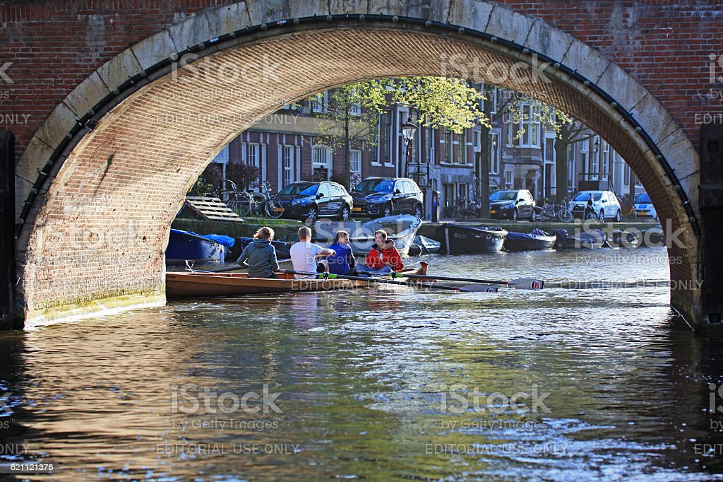 Tourists rowing boat at water channels of Amsterdam, Netherlands stock photo