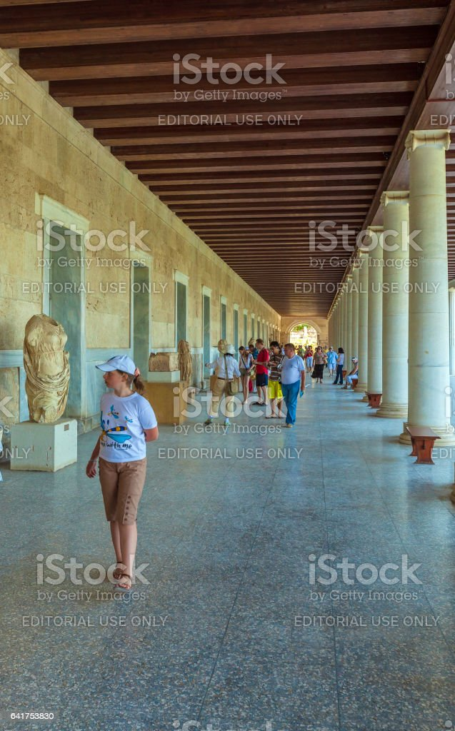 ATHENS, GREECE - JUNE 08, 2009: Tourists showing greek sculptures in Stoa of Attalos at Acropolis stock photo