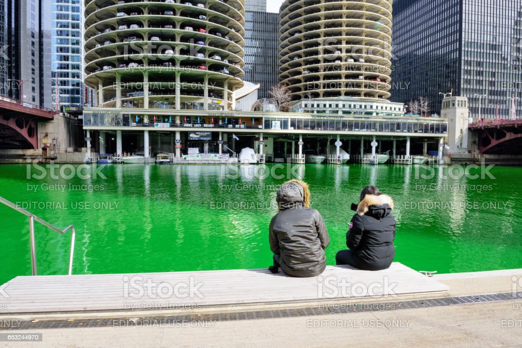 Tourists sitting besides green Chicago River stock photo
