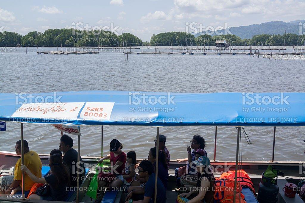 Les touristes assis sur le bateau traditionnel d'huîtres de la ferme photo libre de droits