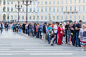 Tourists stand in queue  to the State Hermitage Museum