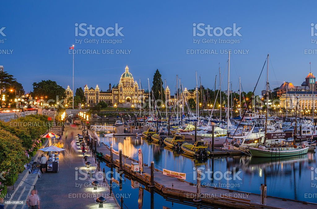 Tourists Strolling the Causeway of Victoria's Inner Harbour at Night stock photo