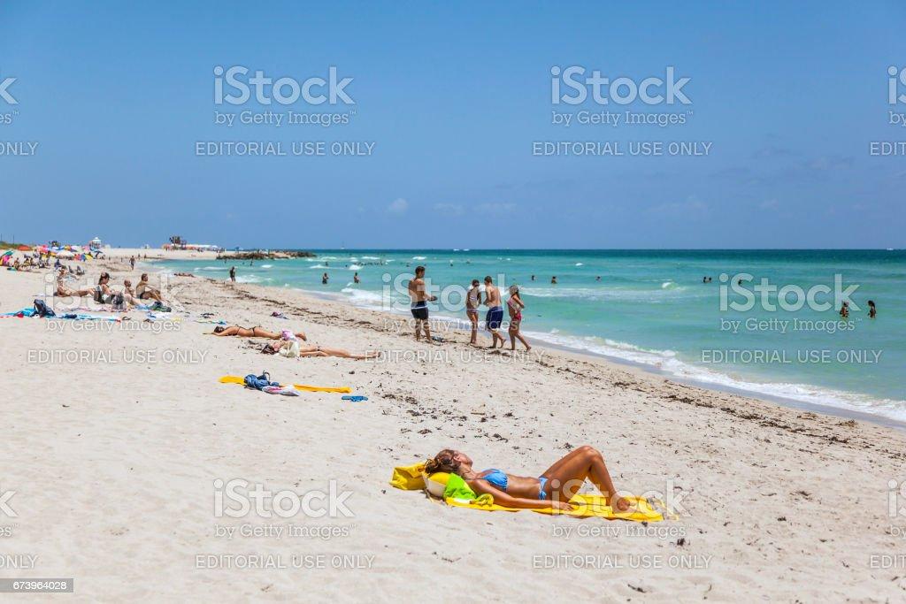 Tourists sunbath, swim and play on South Beach in Miami Beach, Florida stock photo