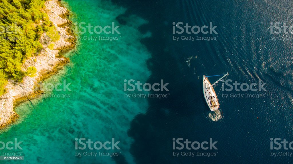 Tourists swimming by the sailboat stock photo