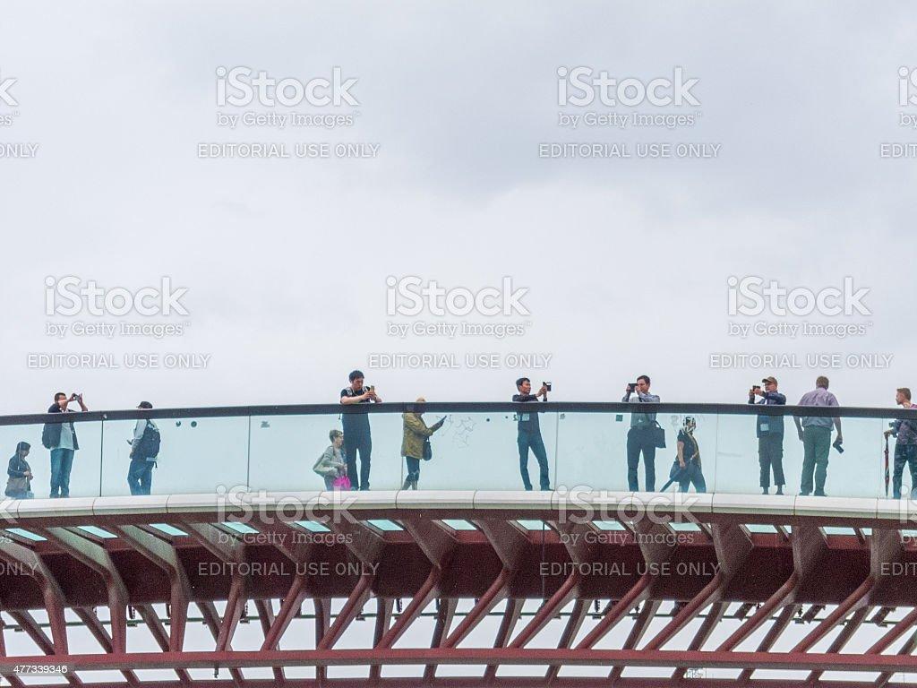 Tourists take photos using smartphones on Constitution bridge, Venice. stock photo