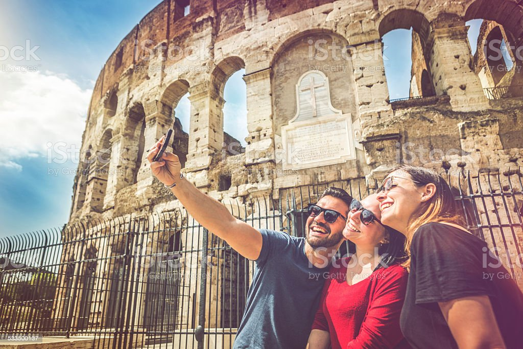 Tourists taking a selfie in front of the Coliseum, Rome stock photo
