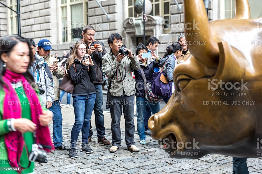 Tourists Taking Pictures of Wall Street Bull, New York City stock photo