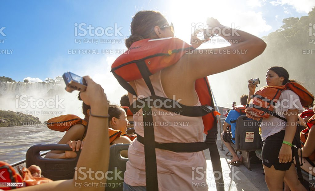 Tourists taking pictures on an Iguazu falls boat tour, Argentina royalty-free stock photo