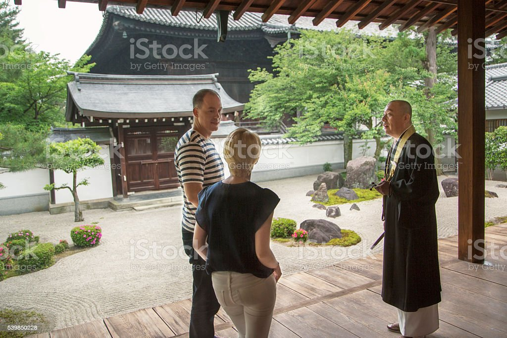 Tourists talking to Japanese Buddhist Priest stock photo