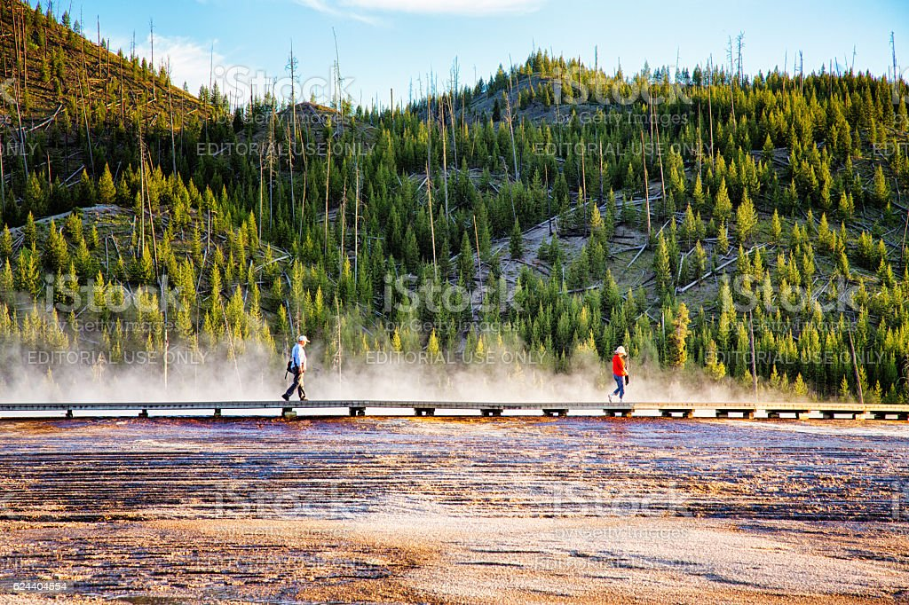 Tourists visiting sulphurous springs in Yellowstone park at sunset stock photo