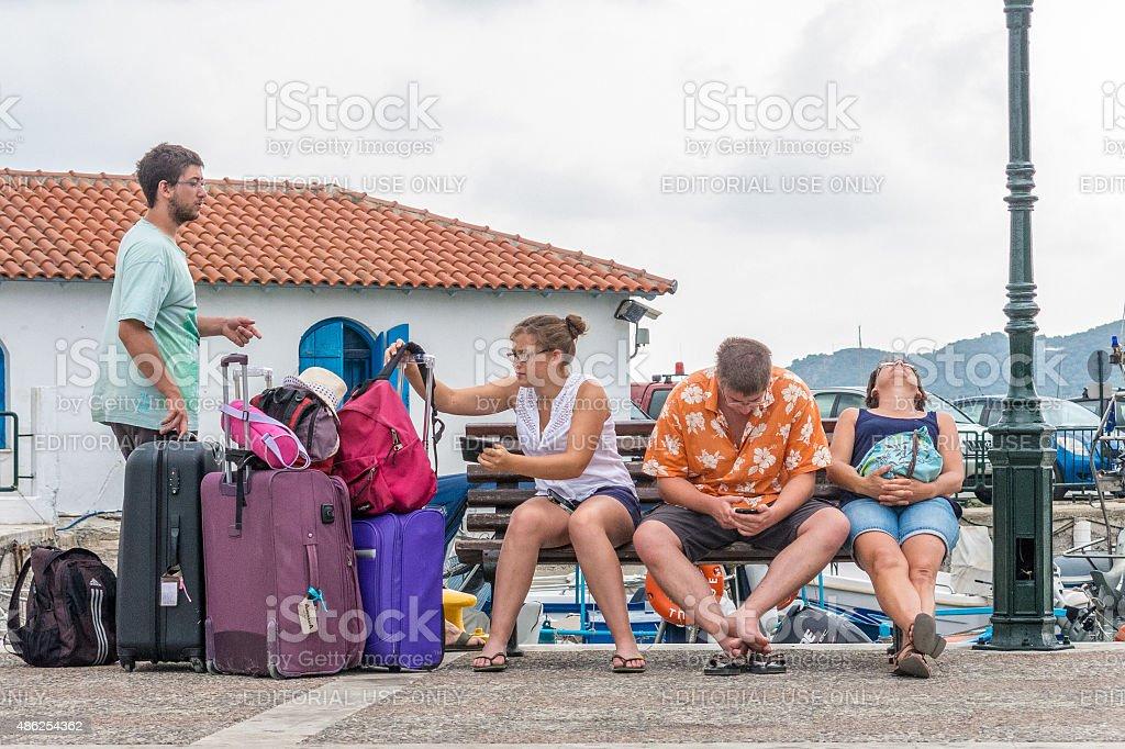 Tourists wait with their luggage at a ferry terminal, Skiathos stock photo