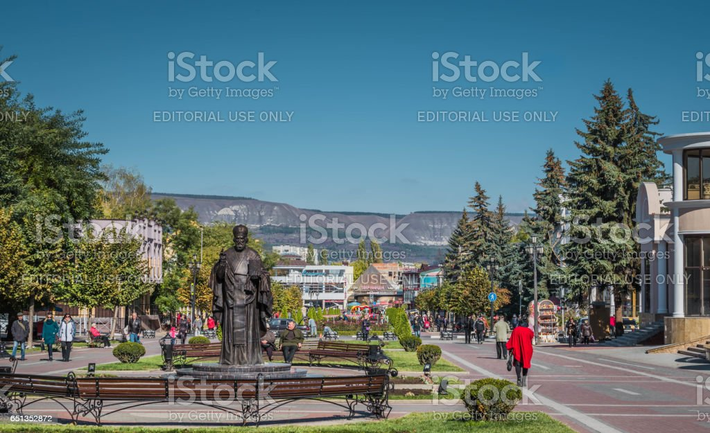 Tourists walk along a beautiful alley in the resort town Kislovodsk, Russia. stock photo