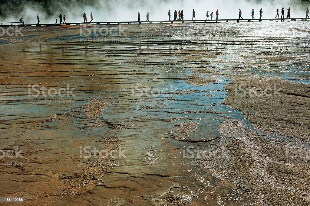 Tourists walk along a boardwalk at the Grand Prismatic Springs stock photo