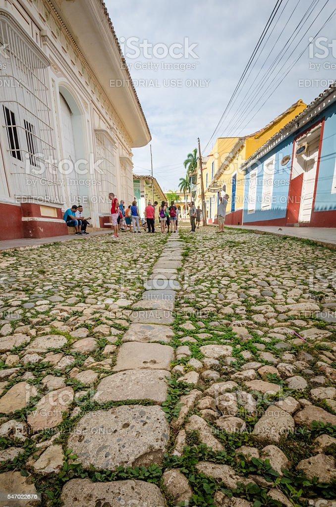 Tourists walk along cobblestone street in Trinidad, Cuba stock photo