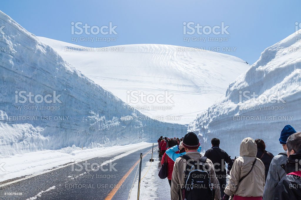 Tourists walk along snow corridor on Tateyama Kurobe Alpine Route stock photo