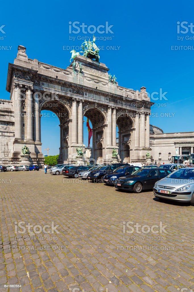 BRUSSELS, BELGIUM - APRIL 5, 2008: Tourists walk in front of Cinquantenaire Arch (1880-1905) stock photo