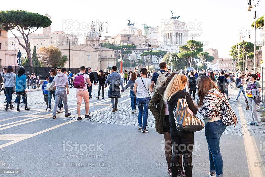 tourists walk on Via dei Fori Imperiali in Rome stock photo