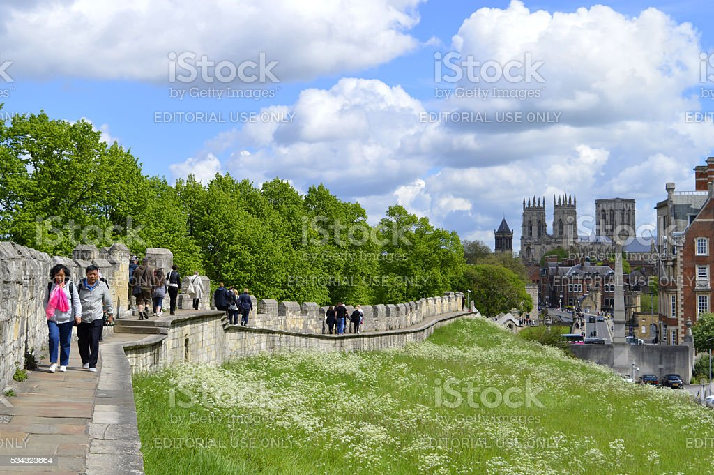 Tourists walking along York City Roman wall surrounding the City stock photo