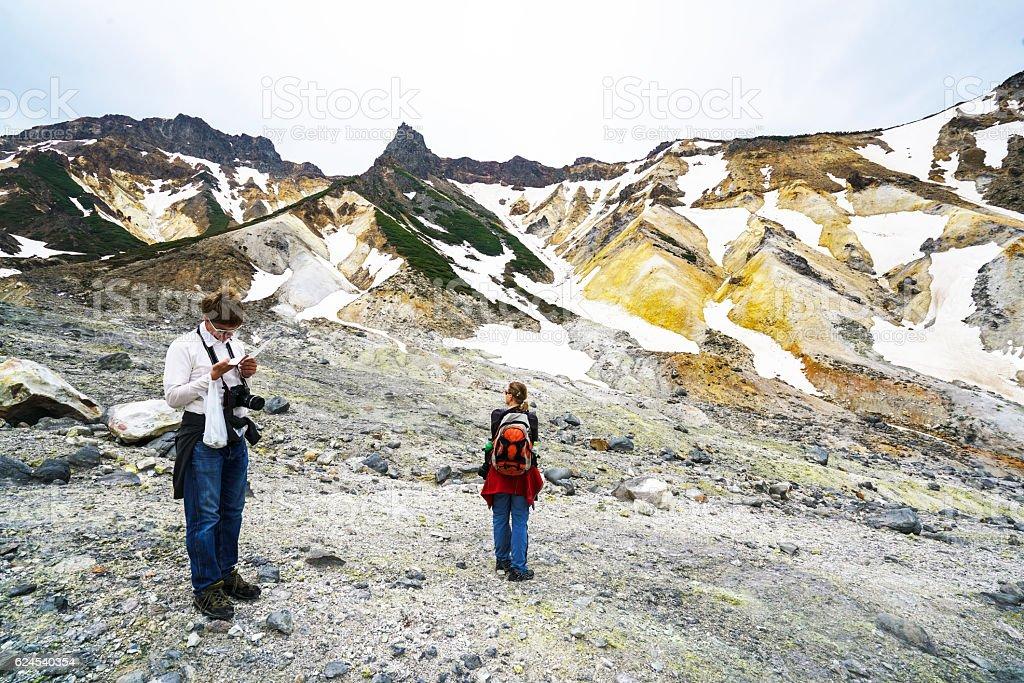 Tourists walking in crater of Tokachidake active volcano, Hokkaido Japan stock photo