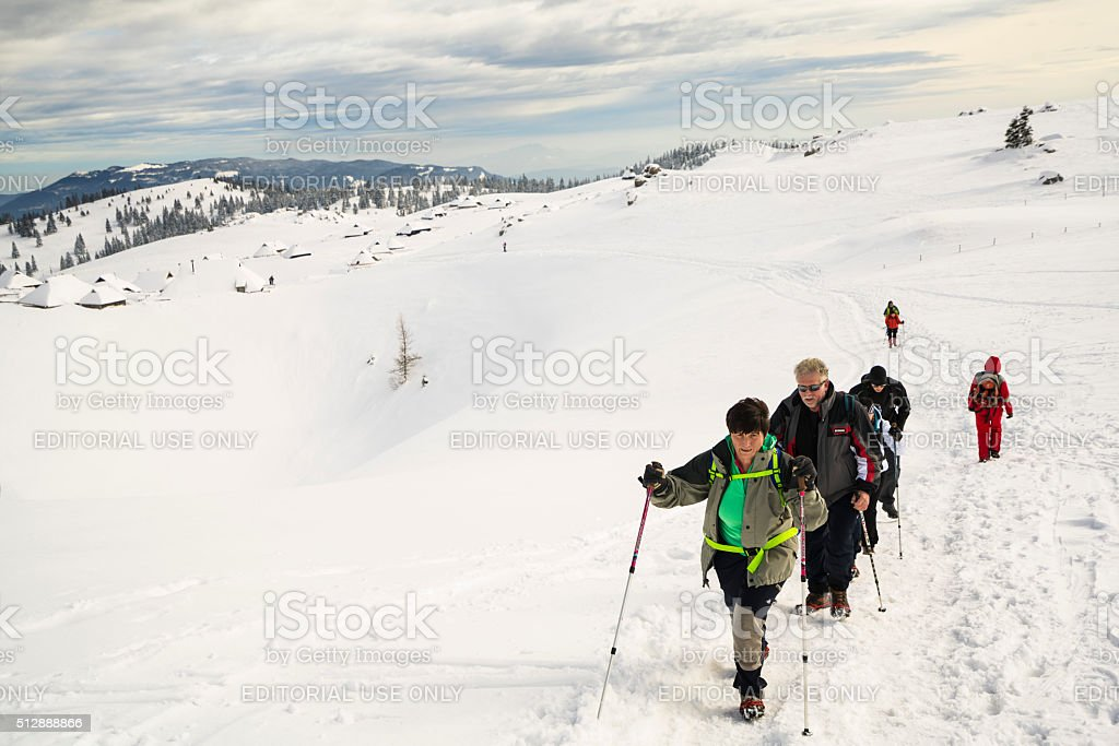 Tourists walking in snow landscape of Velika Planina, Slovenia stock photo
