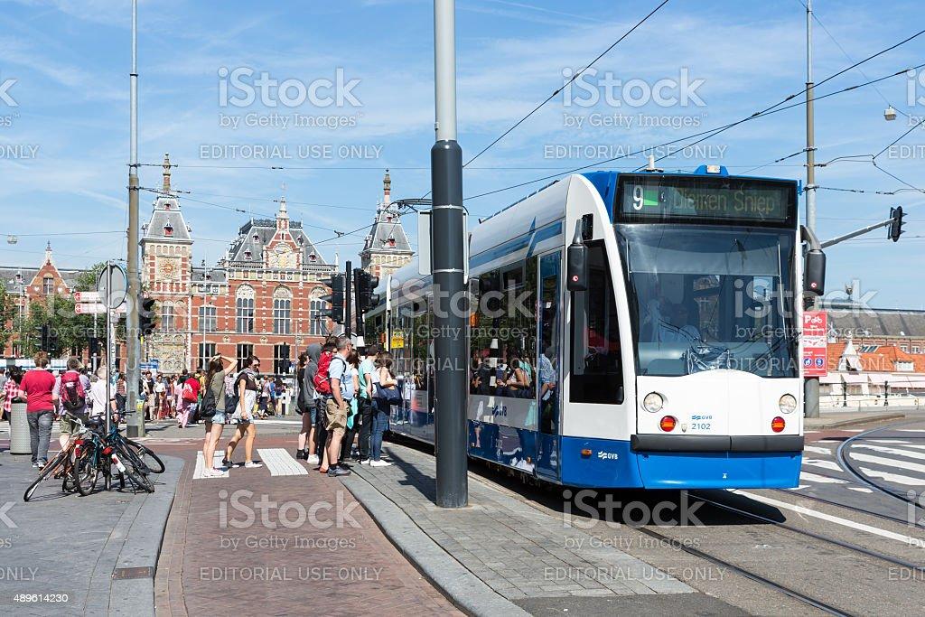 Tourists walking near a tram in Amsterdam stock photo