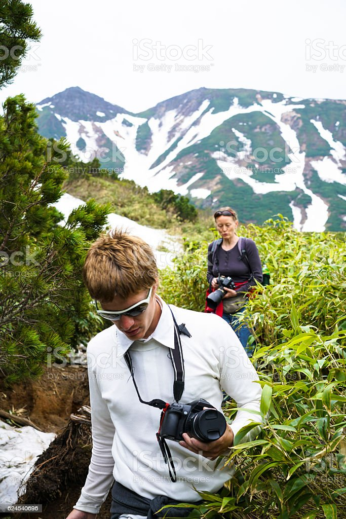 Tourists walking on slope of Tokachidake active volcano crater, Hokkaido stock photo