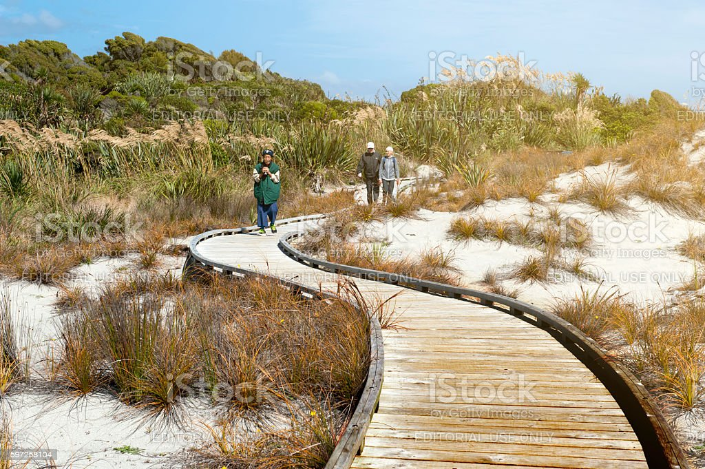 Tourists walking on wooden walkway by the beach stock photo