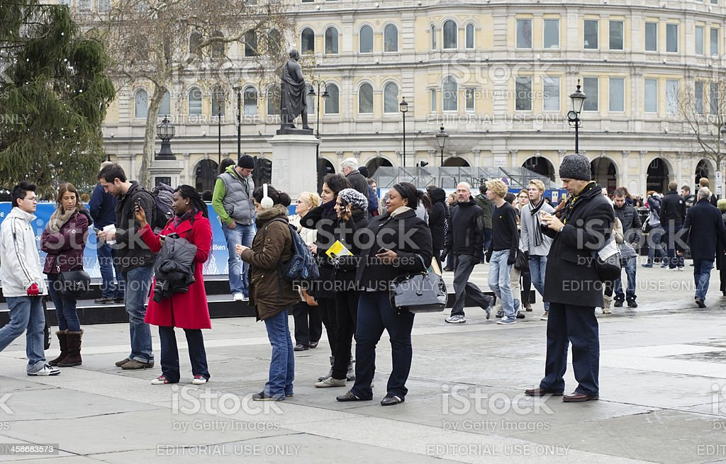 Tourists with camera phones in Trafalgar Square stock photo