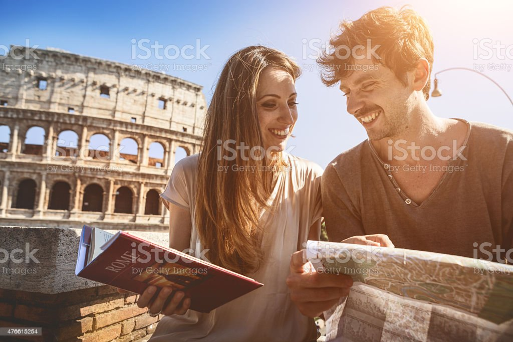 Tourists with guide and map in front of the Coliseum stock photo