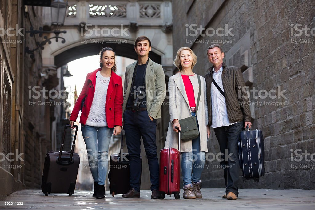 Tourists with luggage pose on the city street stock photo