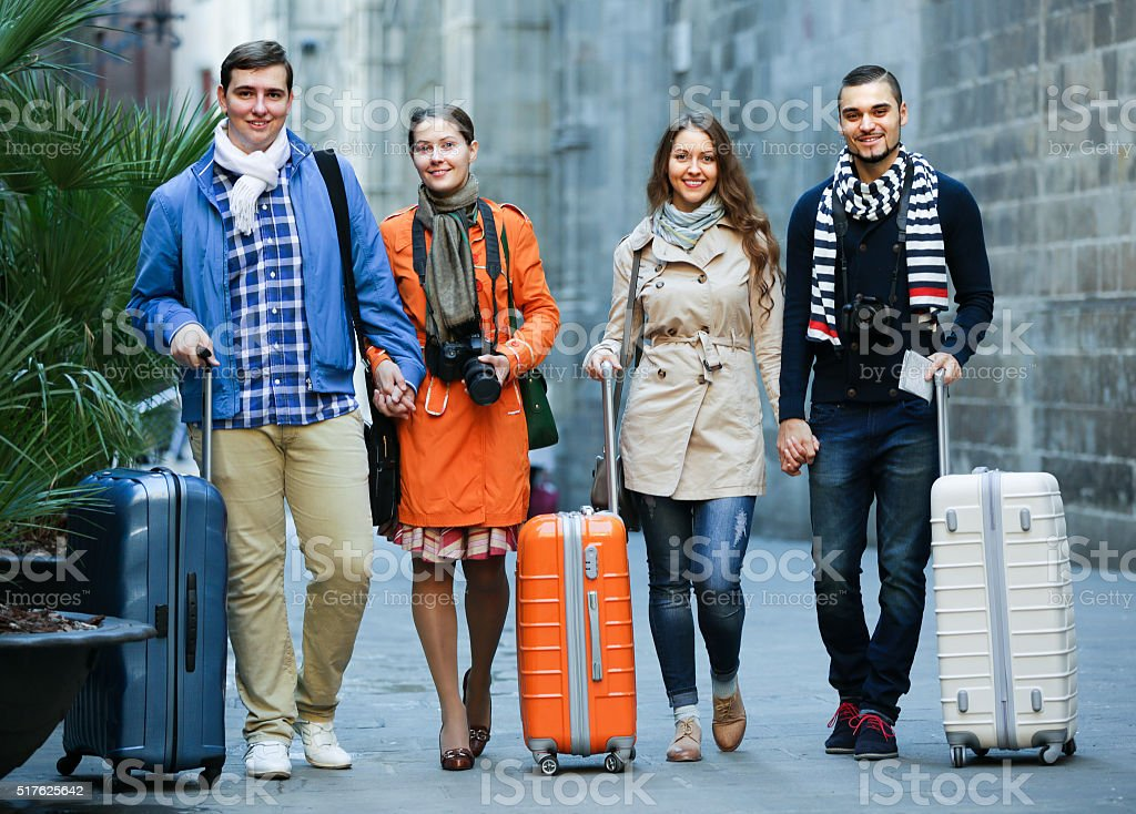 Tourists with luggage walking by street stock photo