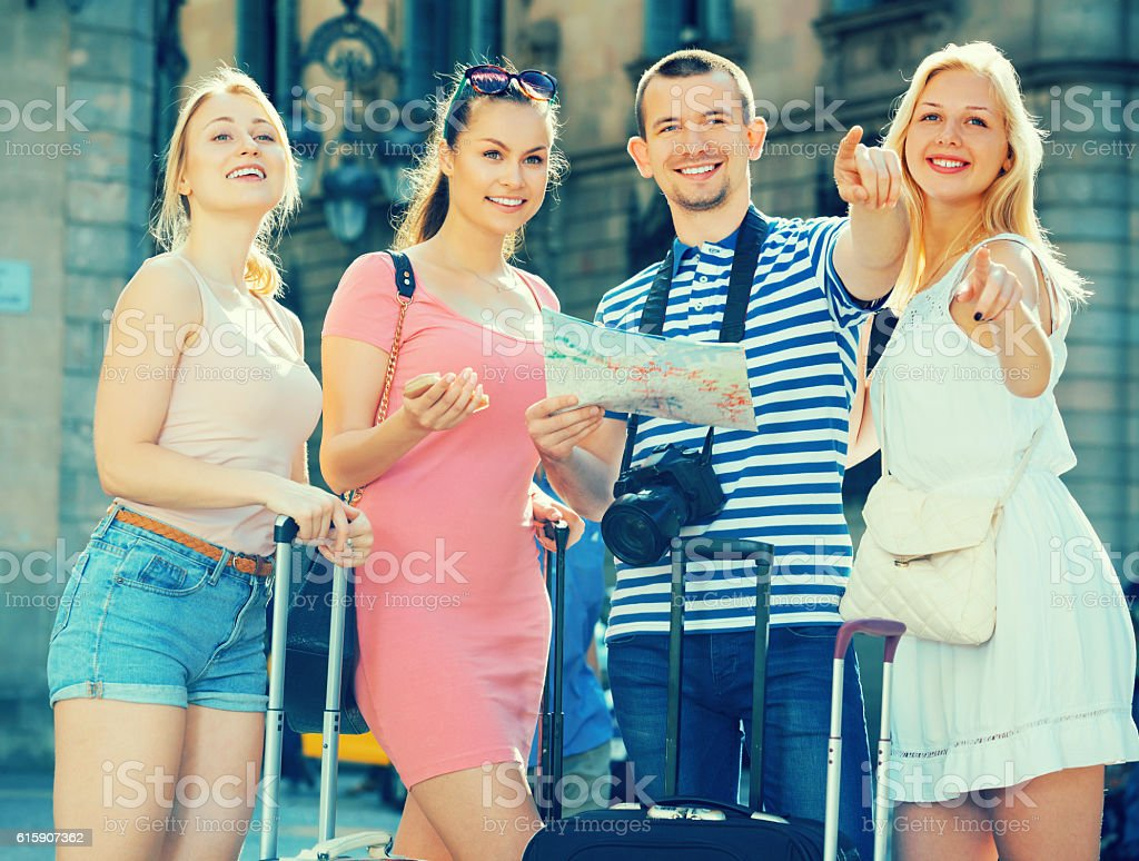 Tourists with map and suitcases stock photo