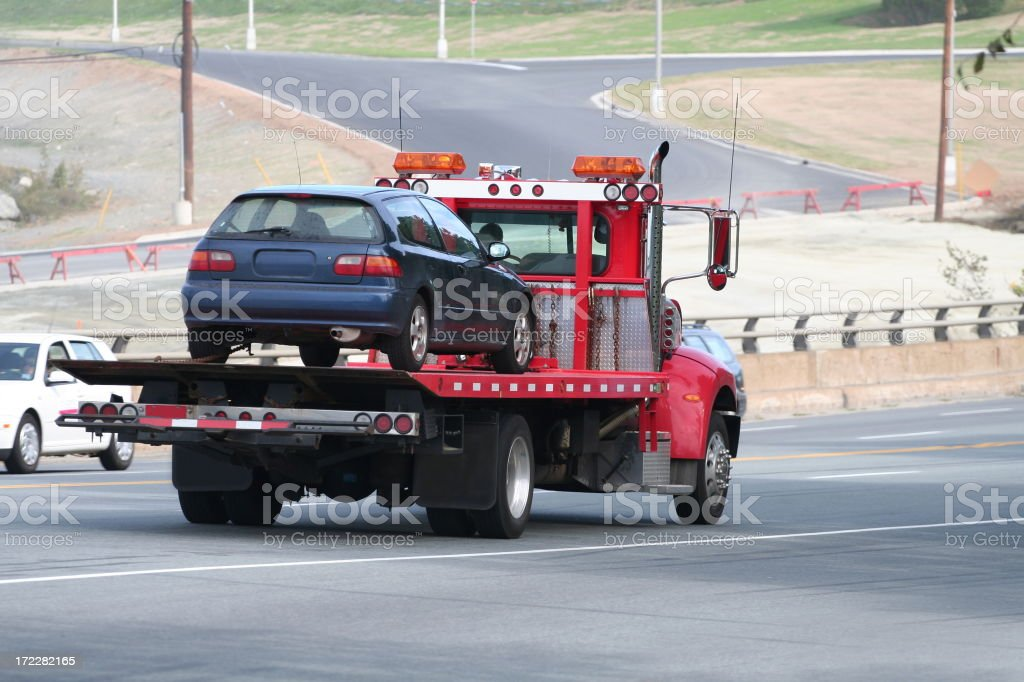 Tow truck carrying car on road royalty-free stock photo