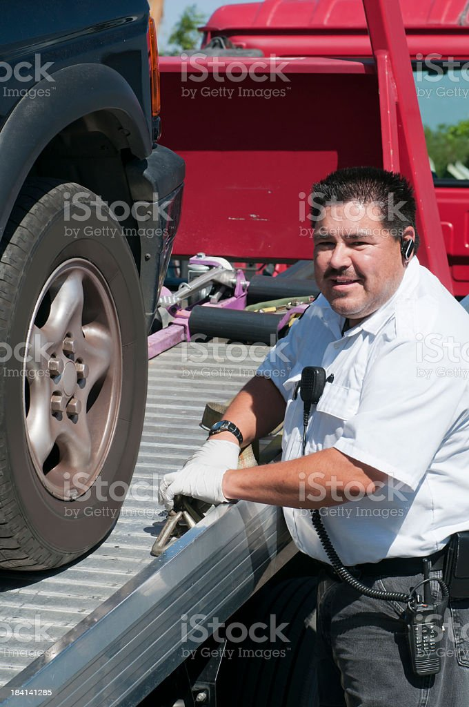 Tow Truck Driver Hauling a Vehicle on a Flatbed stock photo