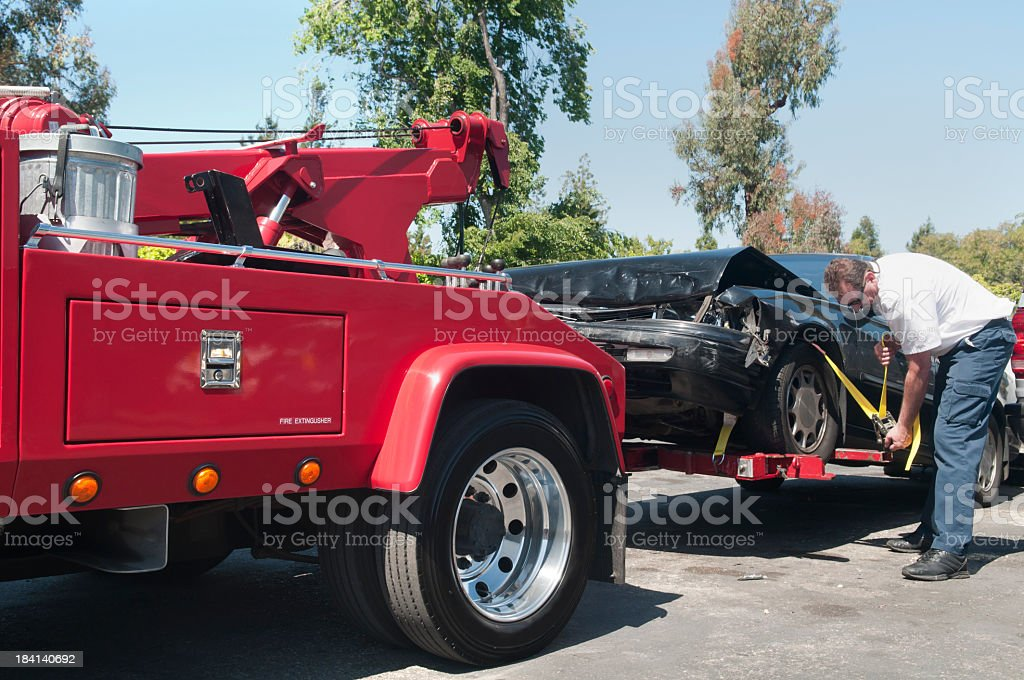 Tow Truck Driver Hauling a Wrecked Car stock photo