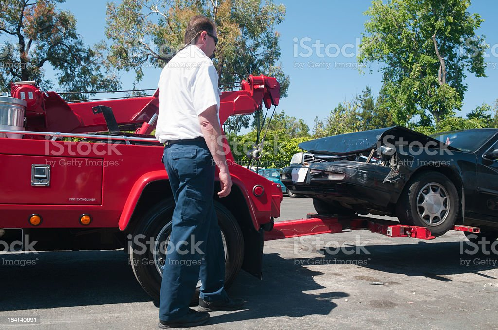 Tow Truck Driver Lifting a Wrecked Car stock photo