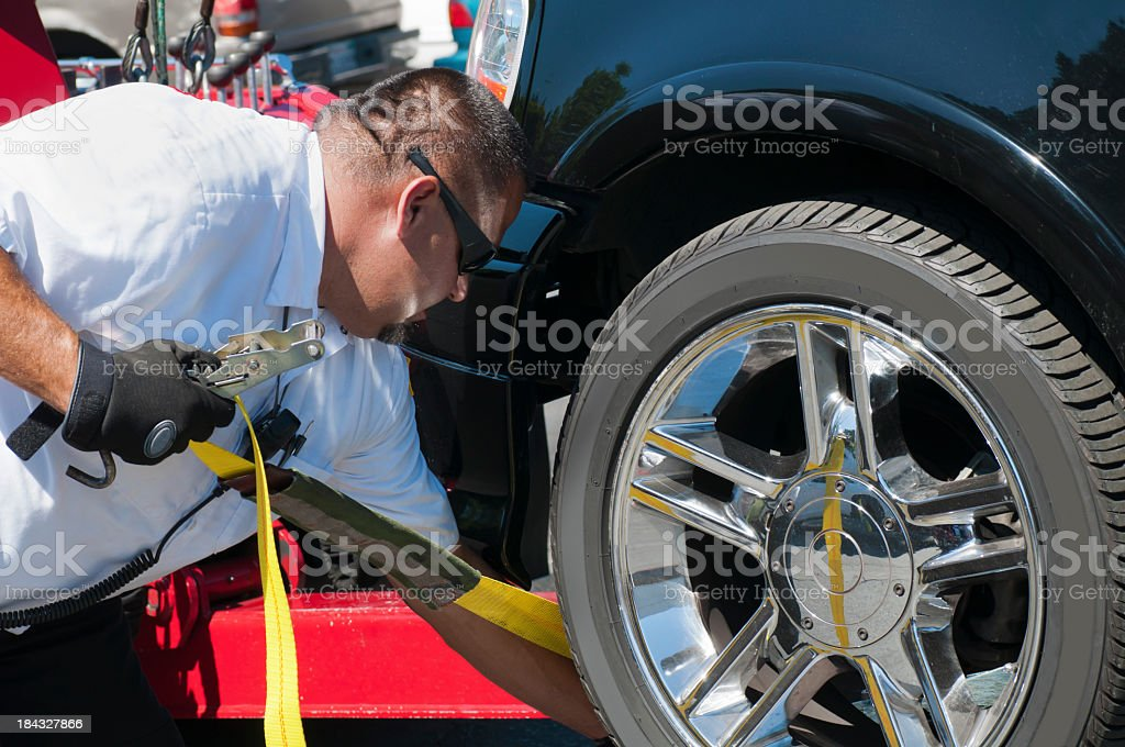 Tow Truck Driver Strapping a Vehicle For Towing stock photo