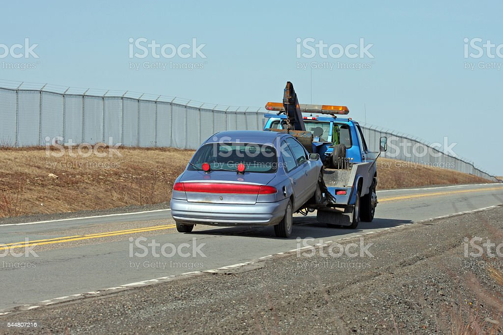 Tow Truck Towing A Vehicle On A Two Lane Highway stock photo