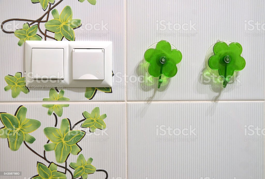 Towel rack, electrical outlet, switch on tilled wall of bathroom stock photo